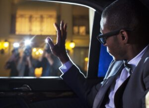 Celebrity in limousine waving at paparazzi photographers